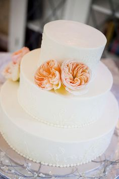 An elegant three tiered white wedding cake is embellished with a couple of peach garden roses.