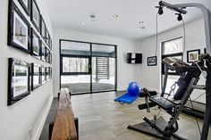 Top 10 Dream Home Gyms - This minimalistic dream home gym – complete with photo wall and rustic wooden bench