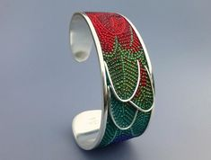 "Courtney Denise Lipson, Macaw Bracelet,Materials: sterling silver, glass seed beads, adhesive, grout Dimensions: 2.5"" x 2.25"" Micro-mosaic cuff bracelet with three-dimensional ruffled feathers."