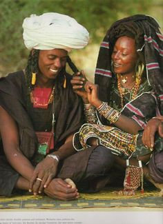 Wodaabe couple. their smiles are priceless. I love how she's doing his hair...