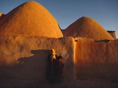 Photo: Woman and child near domed huts