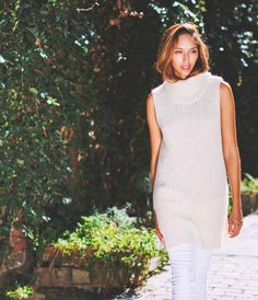 The Creme Knit Sleeveless Turtleneck. Classic fit with side slits. Extra long with ribbed bottom edge and turtle neck. In classic cream or elegant charcoal.