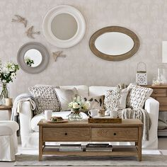 Neutral living room with floral wallpaper, neutral sofa, textured cushions and wood coffee table