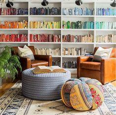 Ein nach Farben sortiertes Bücherregal setzt optische Highlights in der Wohnung.