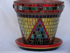 Mosaic terra cotta base planter/flower pot is 6 inches high and 6 inches across the opening. The mosaic work on the pot is a combination of small glass tesserae. It comes with a matching water plate holder. It has a mix of various colored glass tesserae; red, green, black, and a beautiful iridescent gold. It has big triangles all around.