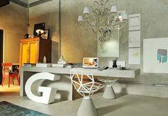 Neste ambiente contemporâneo com parede de cimento, a mesa de concreto parcialmente suspensa serve como escritório ou para refeições