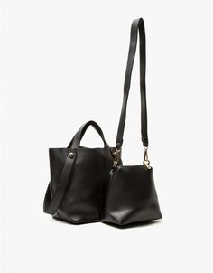 A convertible shoulder bag in Black that can also be worn as a hand bag. Removable shoulder strap. Carrying handles. Main compartment with magnetic closure. Gold-toned hardware. Structured bottom. Unlined. Includes coin purse with wrist strap and large po