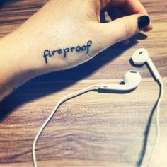 """Pequeño tatuaje que dice """"fireproof"""", palabra en inglés que significa """"a prueba de fuego"""", en la mano de Brens ."""