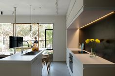 Note the TV on a pole. In the kitchen, the custom cabinets contain special compartments that hide appliances from sight. The room draws in natural light from the balcony.