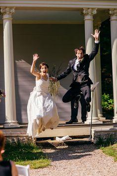 bride and groom take celebratory leap