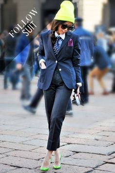 A showgoer balances her tie and pocket square with a pair of pumps in Milan.