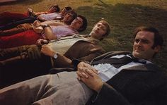 real men lie down in a row on the grass