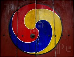 Picture of A Korean traditional symbol on a wooden gate. This symbol is from a temple in Pusan and is the precursor to the Korean flag.