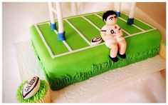 Rugby themed cake, with handmade rugby player and matching rugby ball cupcakes.