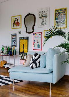 Sala de estar tem sofá azul claro, tapete listrado e parede galeria.