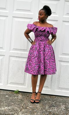 The Balma dress in a purple bold print, a cutie reminiscent of the 50s. It has a wide collar at the shoulder and elastic smocking at the waist and back giving a snug and flattering fit. The skirt of the dress is full and dainty. A dress that could be dressed up or down. The dress may be