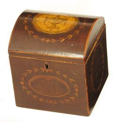 A Regency harewood and marquetry inlaid domed top tea caddy, the front with an oval oyster panel with a leaf border, the hinged top inset an oval print depicting a classical urn, 13.5cm (5.25in) h, 12cm (4.75cm) w.   Woolley & Wallis