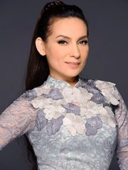 Hình ảnh ca sĩ Phi Nhung rạng rỡ với áo dài phối ren tinh tế, kiểu dáng sang trọng, màu sắc nhã nhặn, rất hợp với vóc dáng và tính cách của cô