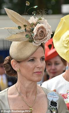 Stylish: A lady arrives wearing a neat brown cocktail hat enlivened with silk roses and feathers