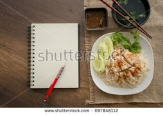 """Chicken Rice with sauce, soup and note boook """"Khao Man Kai"""" on wooden desk (Hainan Chicken)"""