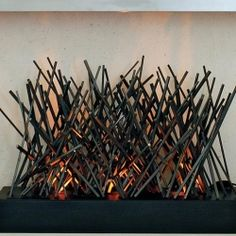 "BD Design's steel fireplace sculpture ""Bonfire"" brings the idea of burning branches inside the house with steel rods that glow in the fire and crackle and pop sounds as the steel expands"