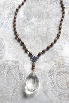 A vintage chandelier crystal is the center piece of this beautiful boho style necklace. It hangs from a bronze ornate center piece. The chain is made from vintage wooden french rosary beads. The beads are in absolutely beautiful condition, smooth with a slight luster and no wear.