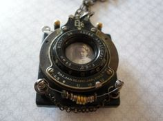 This a unique, one-of-a-kind mixed media necklace by Jen Crossley. This necklace features an old camera lense as the frame for the vintage photo of a