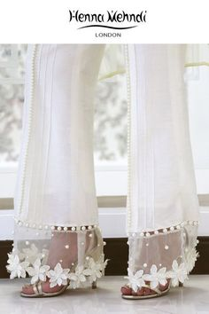 Designer Indian & Pakistani White Embellished Trousers available in Salwar Trousers, Embroidered Trousers and Bootcut trousers. Designed in London UK. Free delivery over £75. White raw silk trousers with 3D flowers and pearl embellishment. ̴Ì_These trousers can be ordered in black or white. Please note delivery time is approximately 4-6 weeks. There is no exchange or refund̴Ì_on this product as this item will be customised especially for your order. Salwar Designs, Blouse Designs, Fashion Pants, Fashion Dresses, Workwear Fashion, Desi Clothes, Designs For Dresses, Pakistani Outfits, Indian Designer Wear