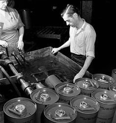 Workers A. Beaudry and Rolland Charboneau operate a machine that tests the airtightness of smoke generators in a tub of water at the General Steelwares Ltd. plant / L'ouvrière A. Beaudry  et son collègue Rolland Charboneau utilisent une machine pour vérif | by BiblioArchives / LibraryArchives