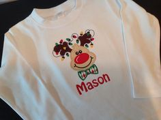 Christmas Reindeer with lights and bow tie is appliqued directly onto a super soft white bib, bodysuit or t-shirt with your child's name embroidered directly below the applique in your choice of font style. Choose from boy's crew neck t-shirt or girl's lettuce edge t-shirt. Choose your favorite font style here .  Leave information in boxes below.