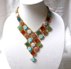 "For your consideration is a beautiful vintage Swoboda authentic gemstone Egyptian revival style bib necklace. This beautiful necklace makes quite the statement with the round discs of genuine gemstones in turquoise, green, brown, rose, amber and green colors. Connecting each stone are gold plated twisted metal loops. The stones each measure approximately 9/16"". The drop where the point of the ""V"" is, measures approximately 5"". It measures approximately 17.5"" long. It comes with the origi..."