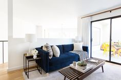 Homepolish's Orlando Soria's Condo featuring this cozy blue couch from west elm.
