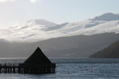 Scottish Crannog Centre on Loch Tay with a snow capped Ben Lawers behind.