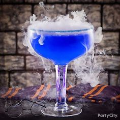 Rim a glass with blue sugar sprinkles; combine vodka, lemonade, and blue curacao; and use tongs to add food-grade dry ice chips. Note: this thrilling drink requires caution! Remind guests not to touch or consume any undissolved dry ice. Cocktails For Parties, Halloween Cocktails, Fete Halloween, Party Drinks, Cocktail Drinks, Halloween Treats, Fun Drinks, Yummy Drinks, Cocktail Recipes