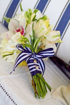Navy + white ribbon with white florals: parrot tulips, peonies, ranunculus, lisianthus, orchids.