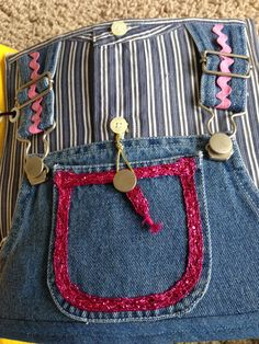 Coveralls with farmer hooks on bib & stretch loop over button to reveal surprise under pocket.