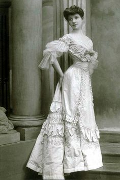 Evening gown by Maison Worth - 1905. Floor-length gown in silk taffeta, tone on tone embroidered with rose pattern. The narrow, high waist is accented by an incorporated corset belt. Deep neckline bordered with draped tulle and accented with applied loop. Three-quarter-length sleeves are also made of draped and shirred tulle. [Photo: Léopold-Émile Reutlinger. State Museum of Berlin]