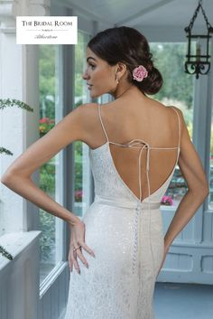 The flirty back details create a fun focal point of this slim A-line gown. A bikini neckline with satin bias belt at the natural waist made the gown delicate. The sequinned allover Chantilly lace embraced the look.