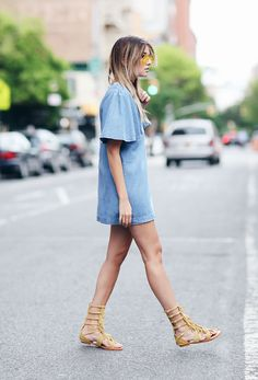 Danielle Bernstein of We Wore What wears a lightweight denim dress with yellow suede gladiator sandals