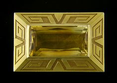 Art Deco!  A dramatic Art Deco brooch set with a beautiful honey-colored Citrine. The gold sides of the brooch rise up pyramid-like to support the gemstone. They are decorated with a boldly geometric Greek key design. Crafted in 14kt gold, circa 1930.