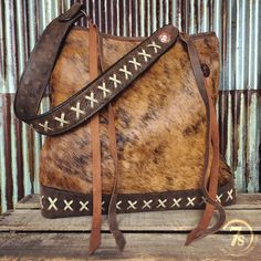 - The softest rustic brindle and leather tote - Beautiful distressed brown bomber natural leather back, bottom and strap - Ivory cross buck stitch accented strap and base - Double hammered copper conc