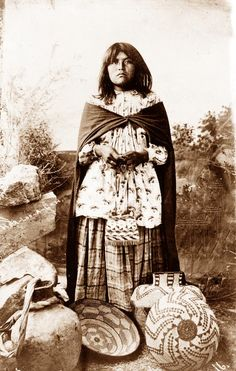 Apache Girl    You are viewing an original photograph of an Apache Girl. The photo is by Gentry, and was taken in 1908. The picture shows Apache Girl and her basket and pottery work.