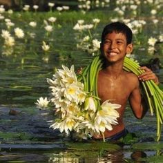 boy with flowers in pond, Thailand