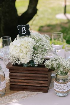 Baby's breath and hydrangeas inside wooden centerpiece boxes.