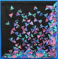 """Wall Quilt 18, """"Tumbling Triangles"""" by Christy Gregg  """"This quilt was my entry for the Tallahassee Chapter of the American Sewing Guild's 2017 Fabric Challenge. You were required to use this bold fabric to sew something. I looked for a way to cut it up enough that I would like the final product. The 2017 Original Sewing & Quilting Expo in Atlanta had a class on this pattern, I took it. I quilted it on my long-arm using free-motion quilting."""" Free Motion Quilting, Capital City, Triangles, Atlanta, Arm, Challenge, Quilts, Sewing, American"""