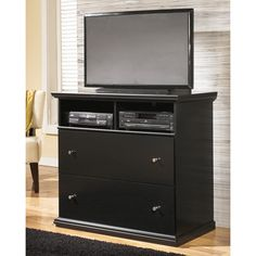 A beautiful black finish adds contemporary style to this classic media chest from Signature Designs by Ashley. Two deep drawers and two open shelves complete the look and function of this timeless chest.