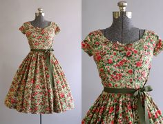 This 1950s cotton Jerry Gilden dress features a floral print in shades of red, pink and green. Short sleeves. Ruching at both waist sides.