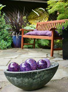 Purple glass orbs garden art, Phormium in a blue pot by KarlGercens.com, via Flickr