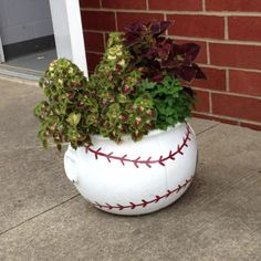 DIY…make a baseball planter…use any round planter..paint it white..add on the baseball stitching.   :-)