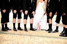 Fun wedding photo: groom and groomsmen lift tux pants, bride lifts white wedding dress to show off p